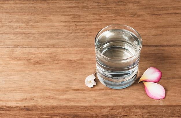 木製のテーブルの上に水のガラス。ガラスとコピースペース付きのきれいな飲料水。