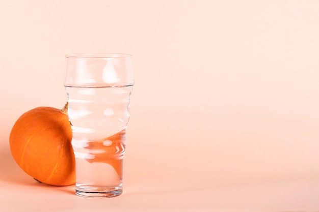 Water glass and pumpkin with copy-space