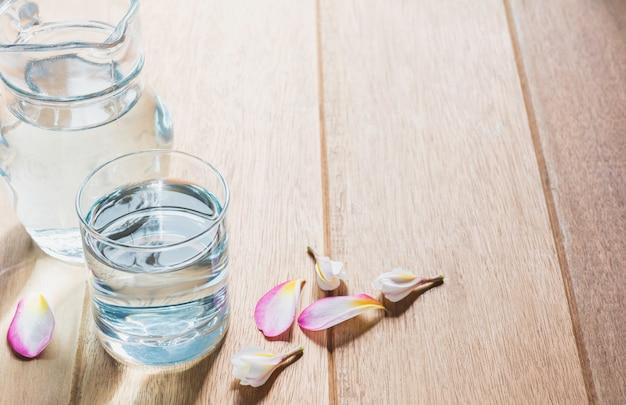 木製のテーブルの上のガラスの瓶と水のガラス。ガラスとコピースペース付きのきれいな飲料水。