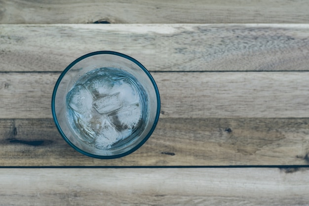 Water in a glass with ice sea lay a wooden floor. focus on the ice behind the blur