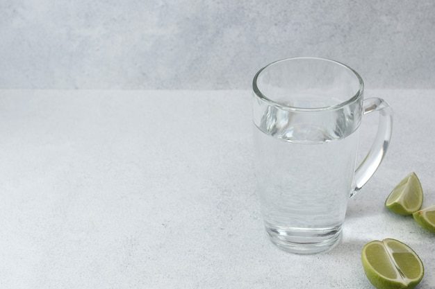 Water in glass with lime on light background with copy space. morning detox drink.