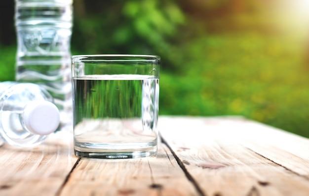 Стаканы для воды и бутылки с водой помещены на деревянные полы.
