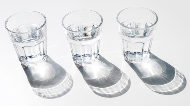 Water glasses with shiny sunlight shadow on white background