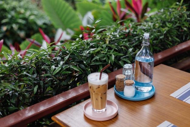 Вода в стеклянной бутылке со льдом латте на розовой подставке, соль и бумага на деревянном столе