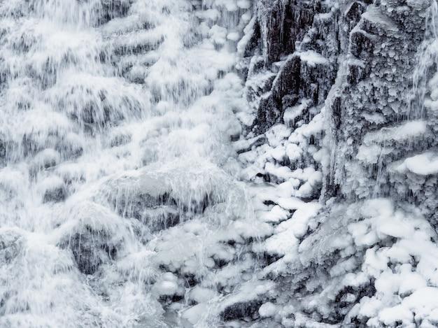 水しぶきで動いている水。氷の滝のクローズアップ。自然な背景。