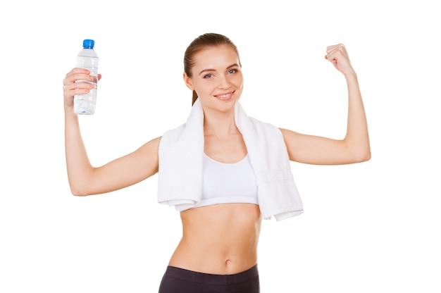 물은 생명입니다. 흰색으로 격리된 채 물병을 들고 몸짓으로 몸짓을 하는 스포츠 의류를 입은 아름다운 젊은 여성