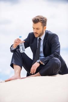 물은 생명입니다. 우울한 젊은 사업가 물이 든 병을 들고 모래에 앉아 있는 동안 그것을 보고
