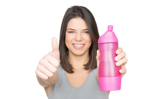 Вода это жизнь. молодая улыбающаяся женщина держит спортивную бутылку и показывает палец вверх селективный фокус