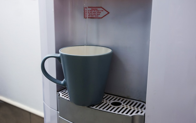 В чашку наливают воду из кулера