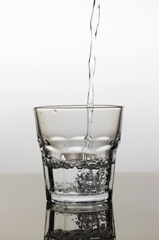 Water is poured into a glass on a light background, close-up