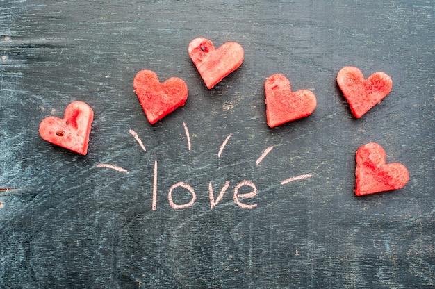 Арбуз нарезать в форме сердца. надпись любовь мелом. день святого валентина концепция