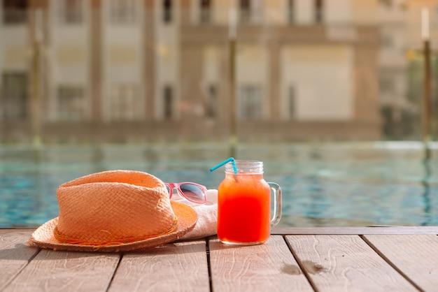 수영장 테두리에 선글라스와 밀짚 모자를 쓴 수박 신선한 과일 스무디 음료 - 휴일 개념