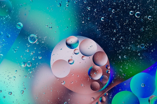 Water oil bubble macro abstract background, flow liquid in blue, pink, white and aqua colors