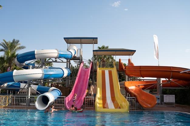 워터파크, 수영장이 있는 밝은 색상의 슬라이드. 맑고 푸른 하늘이 아름다운 여름날, 사람이 없는 워터파크. 고품질 사진