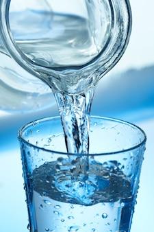 Вода льется из кувшина в стакан на синем.