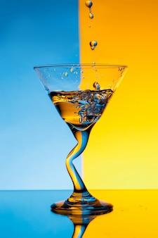 青と黄色の壁の上にグラスに注ぐ水