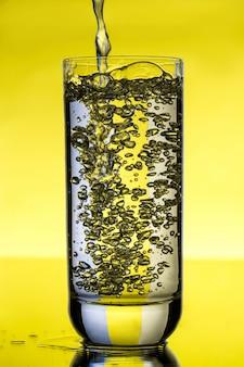 黄色の壁にガラスに注ぐ水