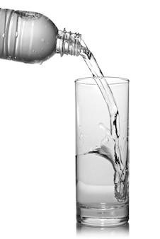 Вода льется в стакан из бутылки, изолированной на белом