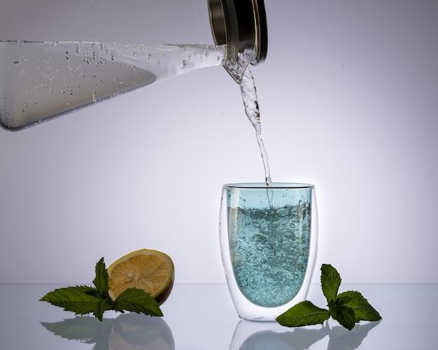투명한 연한 파란색 배경에 있는 유리 디켄터에서 유리에 물을 붓고 깨끗한 물을 마시고 개념.