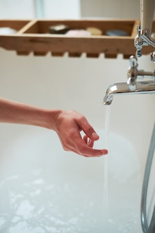 Water pours from the tap in the hands of the girl. the bathroom is bright.