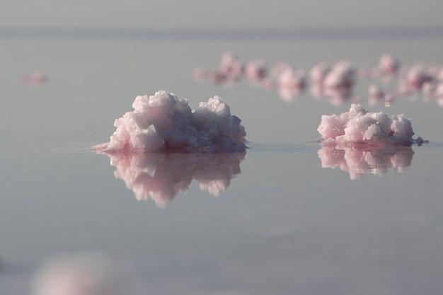 水を反射するピンクの塩の結晶、高い塩分と癒しの特性を持つピンクの湖