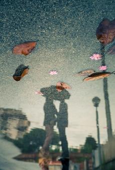 カップルのキスのシルエットと水の反射