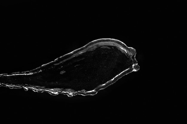 黒の背景に水のしぶき。透明な液体を飛んでいます。透明な水を注ぐ