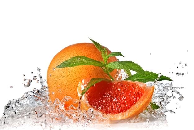 Всплеск воды на грейпфруте с мятой, изолированной на белом