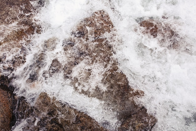 Water splashes against the rocks on the river