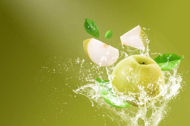 Water splashing on fresh chinese pear and sliced isolated on a green background
