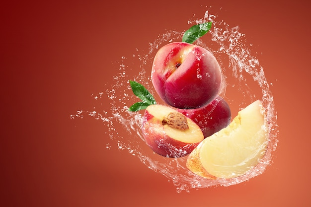 Water splashing and fresh nectarine fruit over red background.