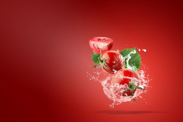 Water splashing on fresh red tomatoes over red