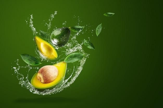 Water splashing on fresh sliced green avocado over the green background.