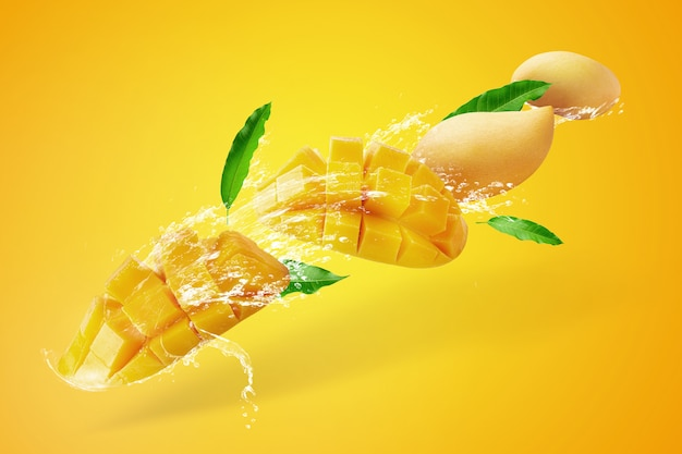 Water splashing on fresh sliced mango fruit with mango cubes isolated on yellow