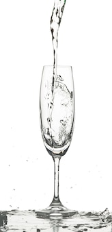 Вода брызгает в стакан на белом фоне