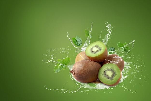 Water splashing on kiwi fruit and half kiwi fruit on green background.