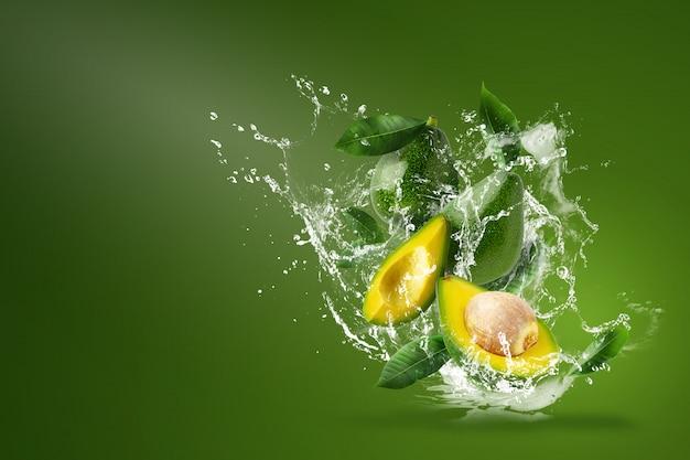 Вода брызгает на свежий нарезанный зеленый авокадо над зеленым.