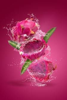 빨간색 배경에 고립 잘 익은 pitahaya 과일에 튀는 물