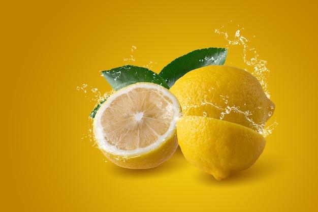 노란색 배경에 분리된 얇게 썬 레몬 과일에 물이 튀는