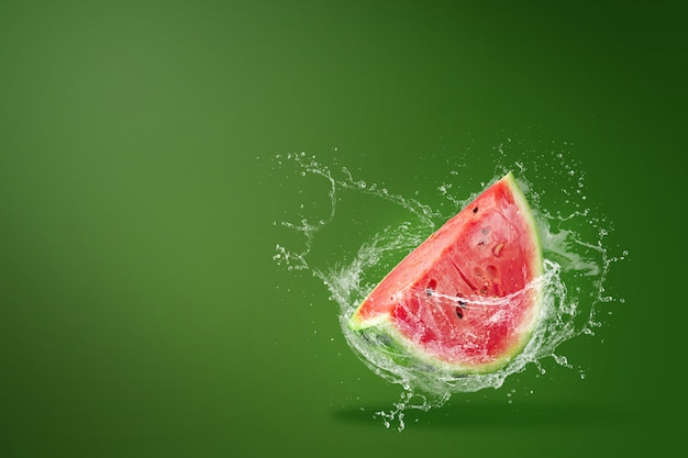 Вода брызгает на ломтики арбуза на зеленый