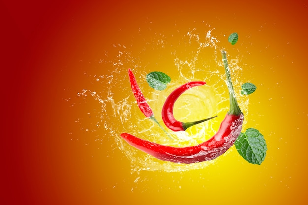 Water splashing on red chili pepper on a red background.