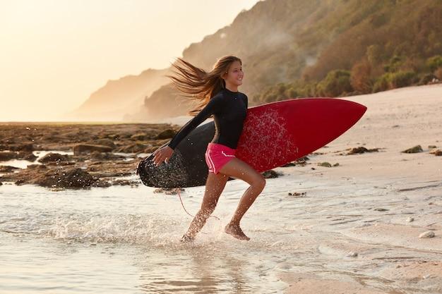 ウォータースポーツとレクリエーション時間の概念。水着を着てビーチを走るハッピーウェーブライダーは前向きな表情