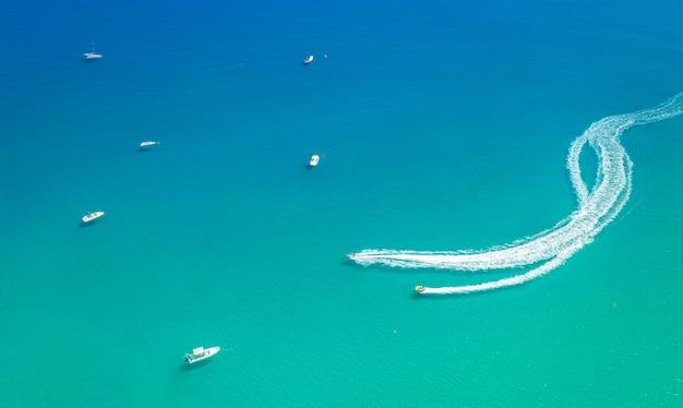슬라이더가 하얀 흔적을 남기는 해변 스피드 보트에서의 수상 스포츠