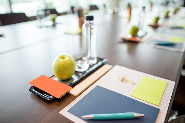 Water and stationery set on conference table