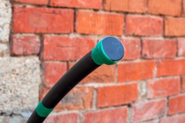 Водопроводная труба полиэтиленовая с заглушкой на фоне сантехники кирпичной стены на даче