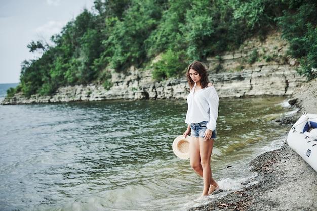 水はすべての悩みを取り除きます。木々と崖の背景とビーチでポーズをとってゴージャスなモデルの女の子。