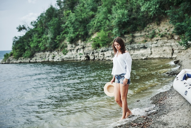 Water takes away all the troubles. gorgeous model girl posing on the beach with cliff background with trees.
