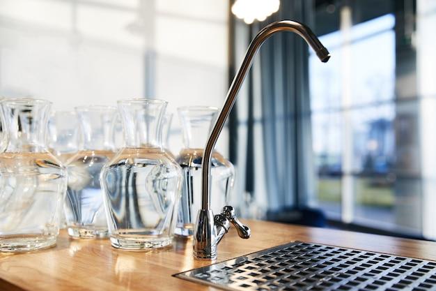 Водопроводный кран рядом со многими большими стеклянными вазами, стоящими на деревянной столешнице