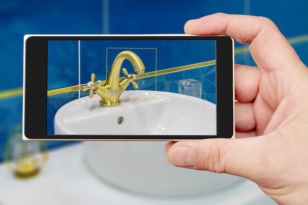 Water tap on smartphone screen. water tap and sink in the bathroom. the interior of the living quarters.