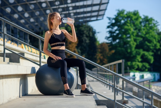 Water time. woman leading healthy lifestyle drinking water before exercising on fitness ball